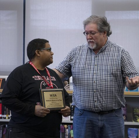 Comeaux holds award with DeMiero standing nearby.